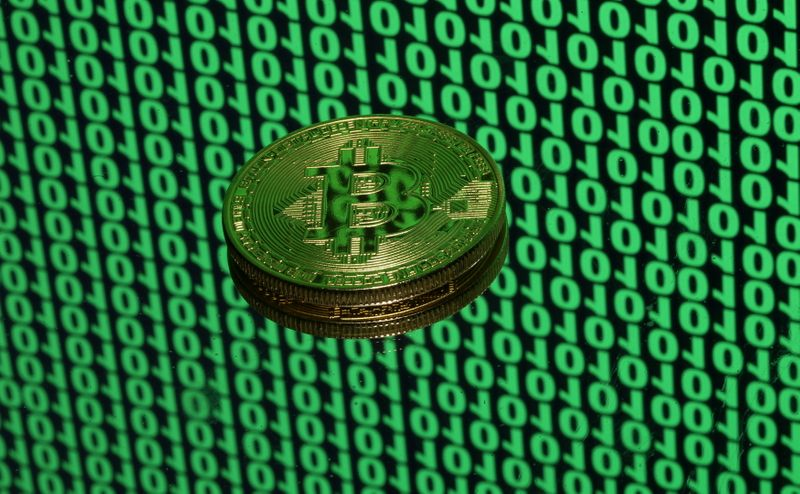 © Reuters. FILE PHOTO: A token of the virtual currency Bitcoin is seen placed on a monitor that displays binary digits in this illustration picture, December 8, 2017. REUTERS/Dado Ruvic/Illustration